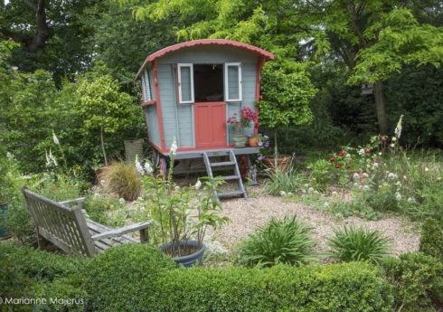 Gypsy caravan on gravel terrace, wooden bench, Centranthus ruber 'Albus', foxgloves, low clipped box hedge