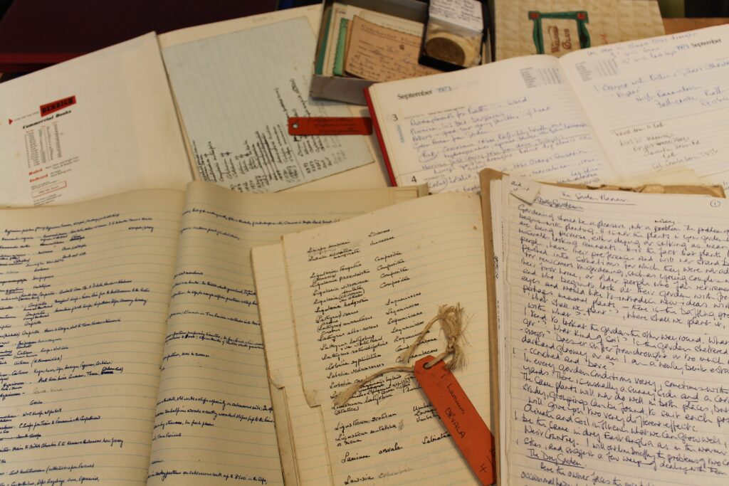 Notebooks, diaries and index books lying open on table.
