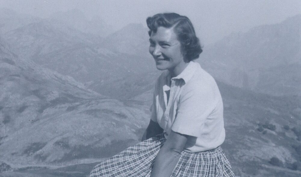 Beth Chatto seated, wearing white blouse and chequered skirt. Mountains in the background.